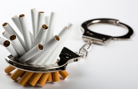 Heap of cigarettes locked to handcuffs Stock Photo - 18400502