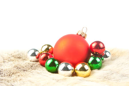 Different color Christmas baubles on fur. Isolated on white photo