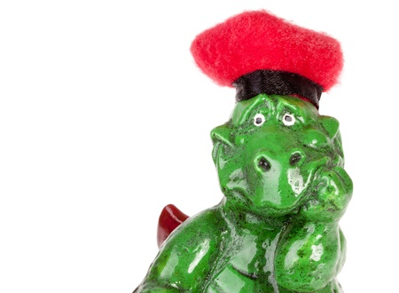 Statuette of funny dragon in red hat. Isolated on white Stock Photo - 18396338