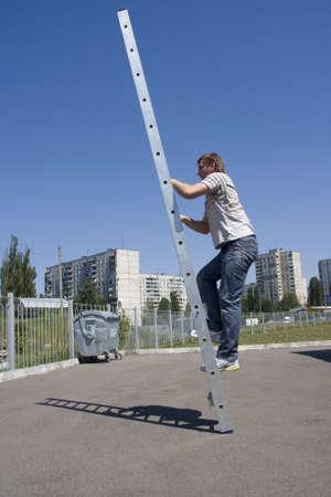climbing ladder: Man climbing ladder. Outdoors