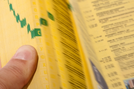 directory book: Hand searching the yellow pages with index finger