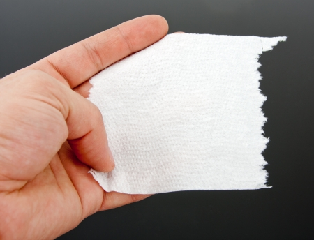 tissue texture: A hand holding one piece of toilet paper. Close-up Stock Photo