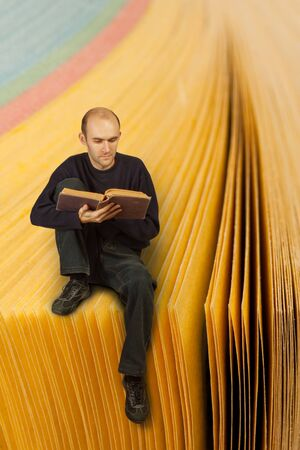 Man reading book on yellow pages catalog photo