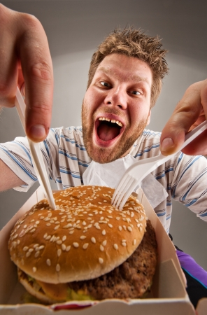 holding a knife: Portrait of happy man with knife and fork eating burger Stock Photo