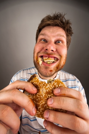 fast eat: Portrait of expressive fat man chewing hamburger