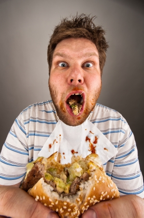 Portrait of surprised dirty man chewing hamburger photo