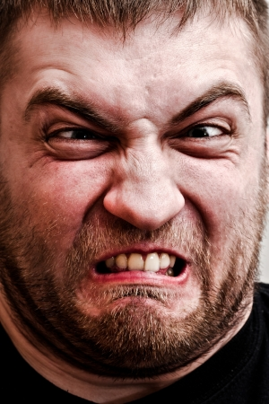 Portrait of strange man making stupid angry face photo