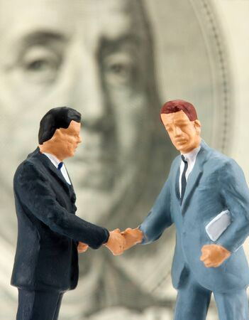 Miniature figurines of two successful handshaking businessmen Stock Photo - 18397785