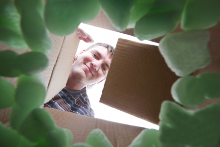 packing supplies: Smiling young man opening into cardboard box Stock Photo