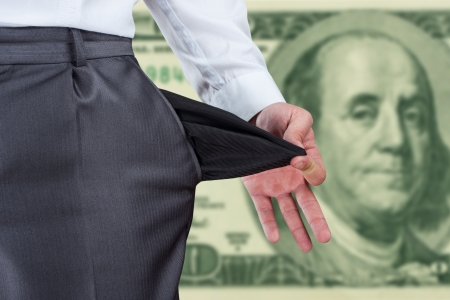 Businessman pulling empty pocket out of pants against dollar banknote photo