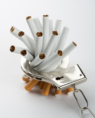 Heap of cigarettes locked to handcuffs. Closeup view Stock Photo - 18430951