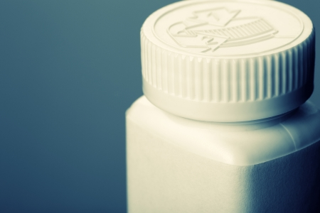 White pills bottle. Toned in blue photo