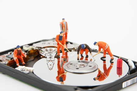 IT support. Workers repairing hard disk drive Stock Photo