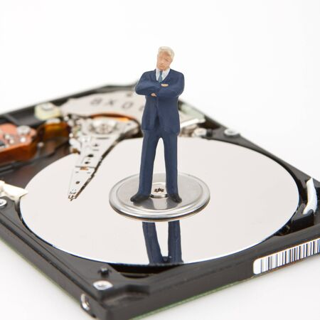 IT security. Businessman on computer hard drive photo