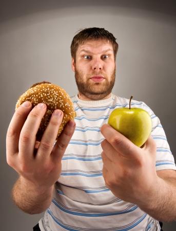 Retrato del hombre que elige entre la hamburguesa y la manzana verde