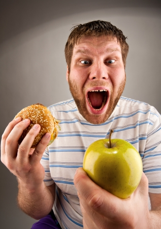 Portrait of man choosing between hamburger and green apple Stock Photo - 18442163