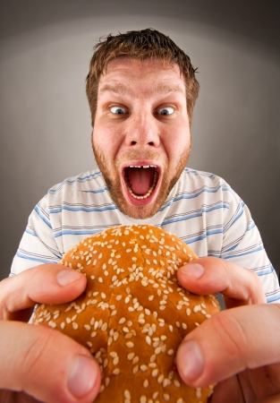 Portrait of expressive man eating juicy hamburger photo
