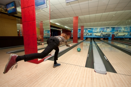 Funny beginner girl playing bowling. Wide angle photo