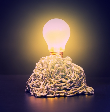 Glowing bulb in ball of chains photo