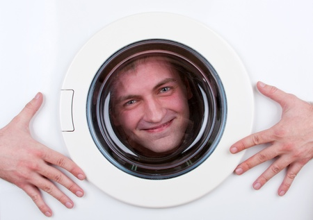Close-up of happy man inside washing machine photo