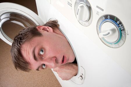 Close-up of surprised man inside washing machine photo