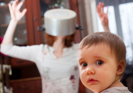 Portrait of scared baby against crazy mother with pan on head photo
