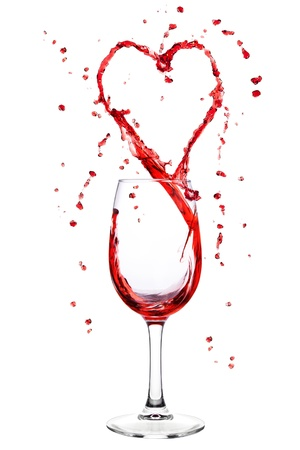 Red wine splashing from wineglass in heart shape photo