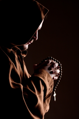 clasped: Monk in robe with two hands clasped in prayer Stock Photo