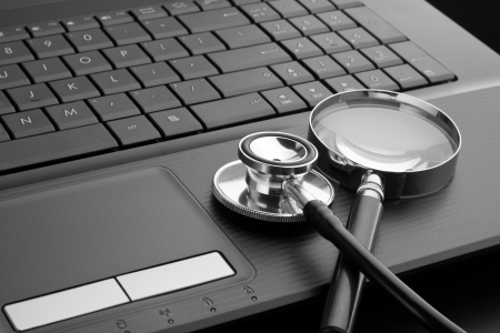 Medical stethoscope and magnifying glass on laptop keyboard. In B/W Stock Photo - 18433536