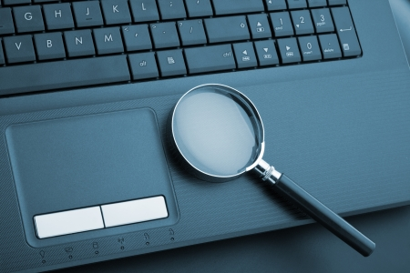 Magnifying glass on laptop computer. Toned in blue Stock Photo - 18433448