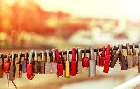 keylock: Old rusty padlocks on bridge railing at morning