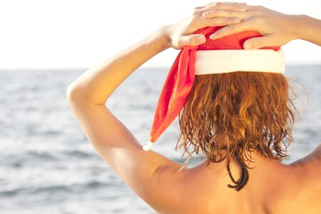 Tan woman in christmas hat looking at the sea photo