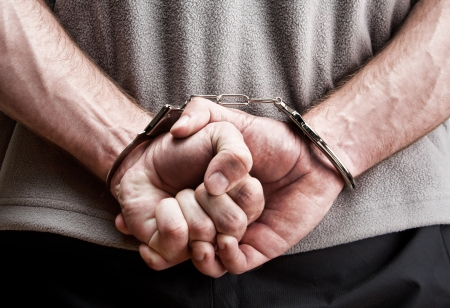 criminal: Criminal hands locked in handcuffs. Close-up view