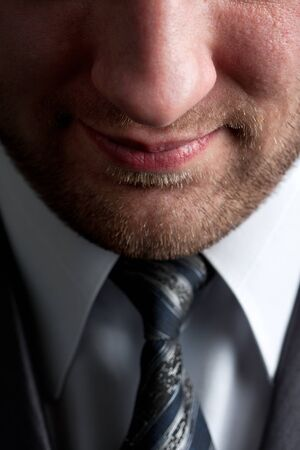 unshaved: Close-up portrait of serious smiling unshaved businessman