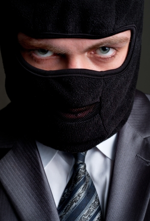 white collar crime: Business crime. Businessman in black balaclava looking to you Stock Photo