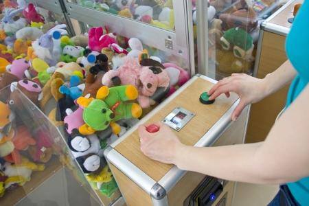 ARCADE GAMES: Woman playing crane machine