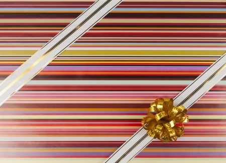 Gold-white ribbon and bow on color gift paper photo