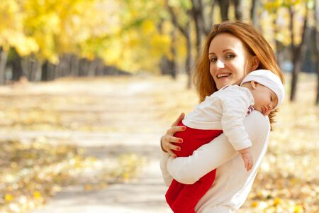 mom holding baby: Happy young mother with sleeping child on hands walking in autumn park