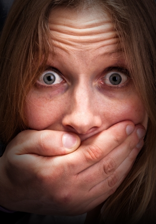 boca cerrada: Miedo chica joven con la boca cerrada a mano