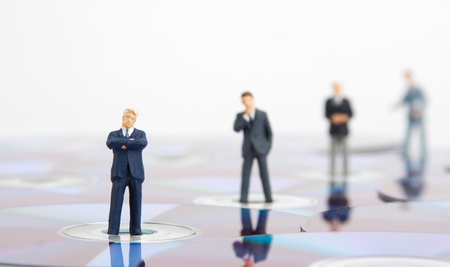 figurines: Small business people standing on computer CDs
