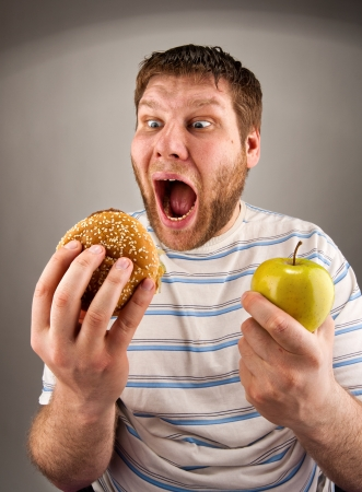 Portrait of man choosing between hamburger and green apple Stock Photo - 18481792
