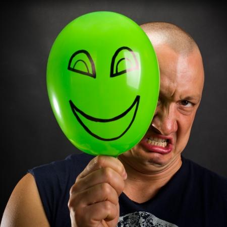 Angry hombre escondido detrás de globo verde con happy smiley