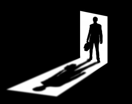 Silhouet van komende zakenman in deuropening met schaduw Stockfoto