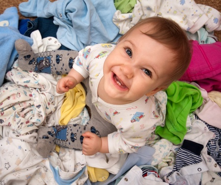 babys: Happy baby girl in heap of babys wear