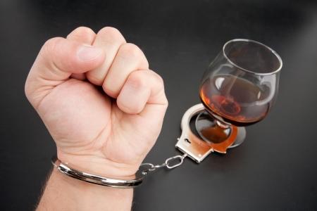 alcoholismo: Una mano cerrada con el vidrio de alcohol por parte de las esposas Foto de archivo