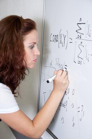 sexy teacher: Student at blackboard in classroom