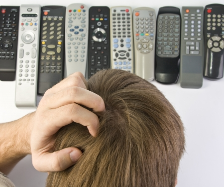 tv panel: Man scratching the head and choosing remote control Stock Photo