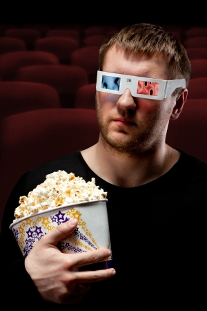 Portrait of man watching 3D movie and holding bucket of popcorn photo