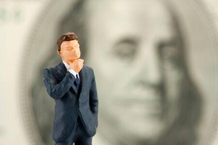 Miniature figurine of wisdom businessman with Franklin on background Stock Photo - 18477921