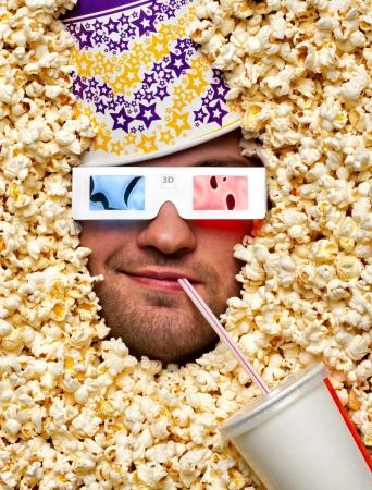 palomitas de maiz: Cara feliz en palomitas de maíz con la cuchara en la cabeza de ver la película en 3D y beber gaseosas Foto de archivo